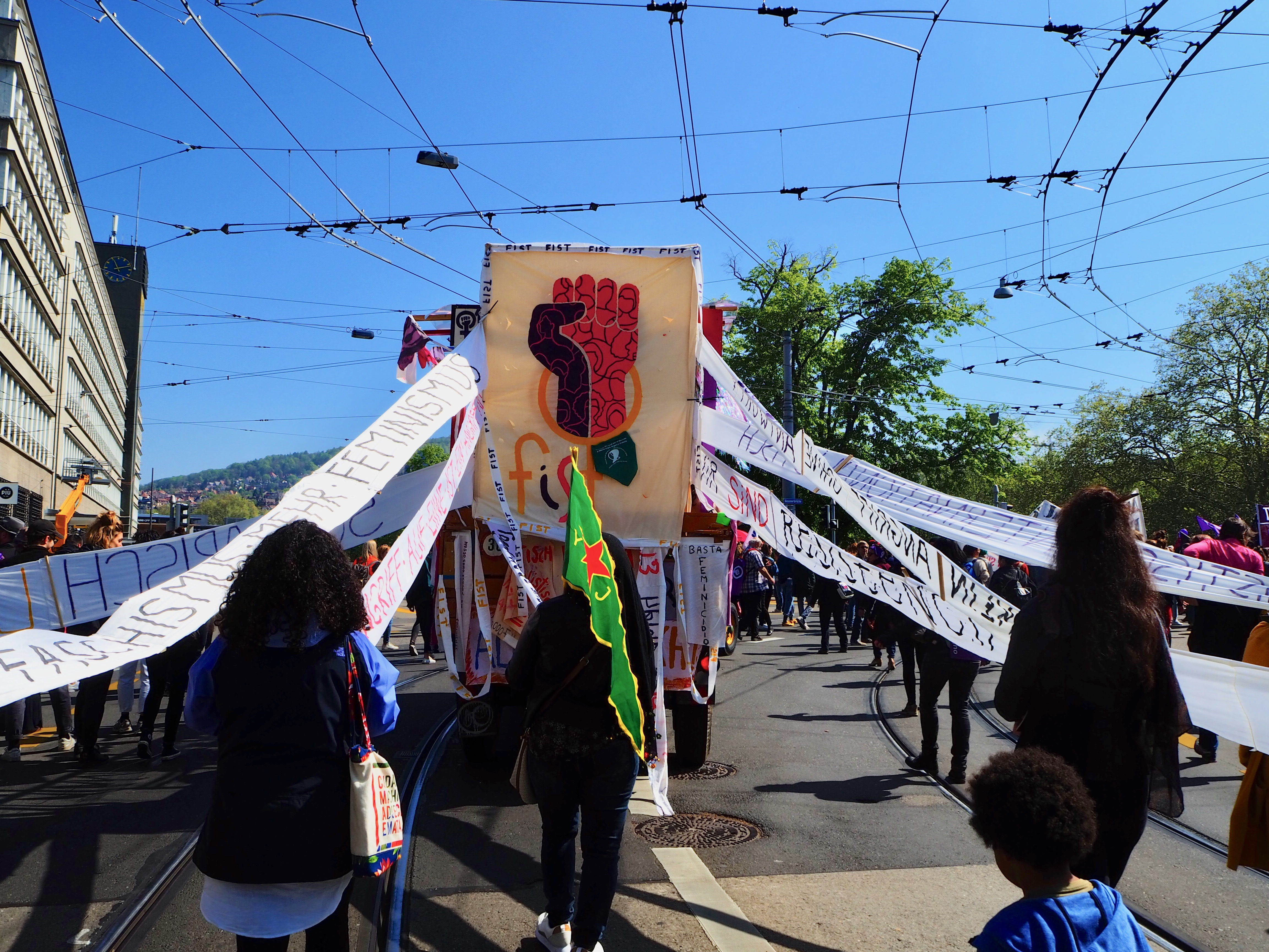 Foto vom FIST Transparent an der 1. Mai Demonstration. Eine Bunte Faust im Feminismus Symbol. Zahlreiche Spruchbänder, auf verschiedenen sprachen beschriftet, sind an dem Transparent befestigt.