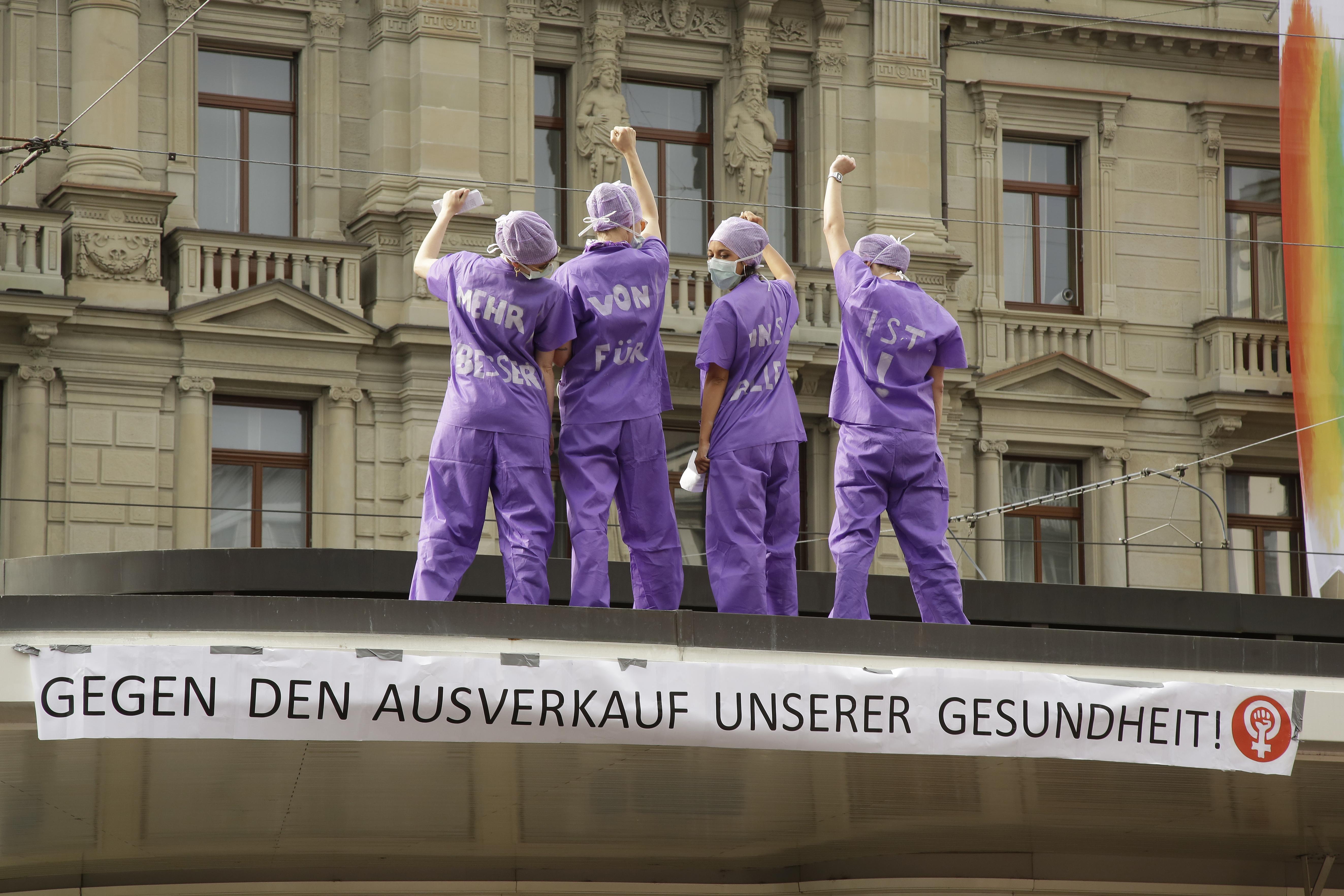 """Foto von Aktion von Pflegefachkräften am 14. Juni 2019 auf dem Dach der Tramstation am Paradeplatz mit Transparent auf dem steht """"Gegen den Ausverkauf unserer Gesundheit"""""""