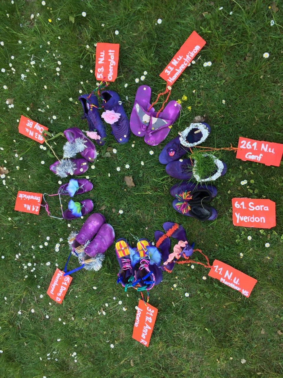Ein Foto von 9 paar violettgeförbte Schuhe jeweils mit einem Schildchen mit jeweils einem Namen und Datum der 9 Frauen, die seit Anfang 2020 bis jetzt (25.4.) ermordet wurden in der Schweiz