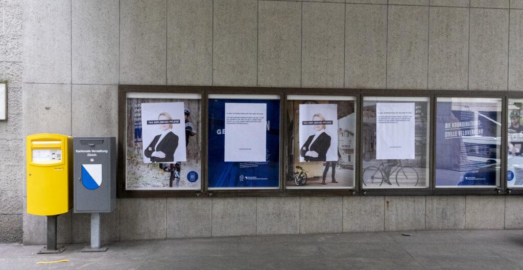 Plakate von Care Work Unite hängen vor der Gesundheitsdirektion in Zürich.