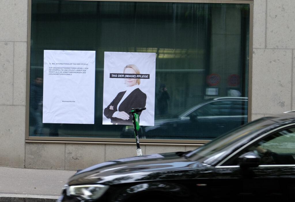 """Plakate von Care Work Unite hängen vor der Gesundheitsdirektion in Zürich. Eine Frau in Anzug hat einen Balken über den Augen auf dem steht """"Tag der (image) Pflege)"""