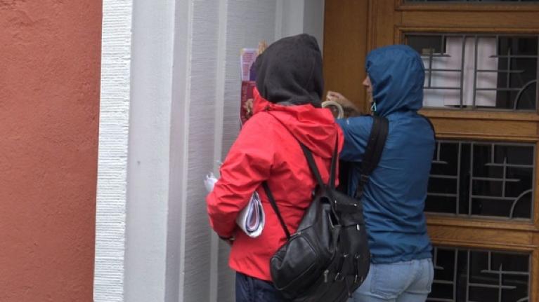 Foto zweier Aktivistinnen von Ni una Menos, die mit Malerklebeband ein Plakat mit Infos zu Frauenhäusern und häuslicher Gewalt