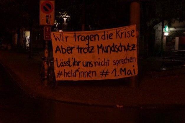 """Foto eines Transparents auf dem steht """"Wir tragen die krise aber trotz Mundschutz lässt ihr uns nicht sprechen #Held*innen *1. Mai"""""""