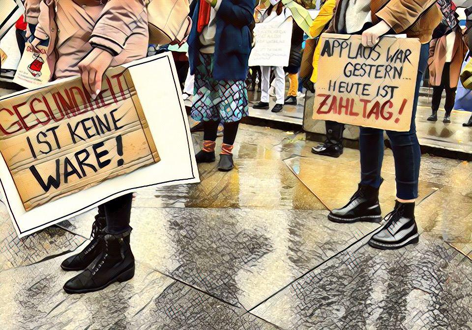 """Zwei Personen, die Plakate in den Händen halten. Auf ihnen geschrieben steht """"Applaus war gestern, heute ist ZAHLTAG!"""" und """"Gesundheit ist keine Ware!"""""""