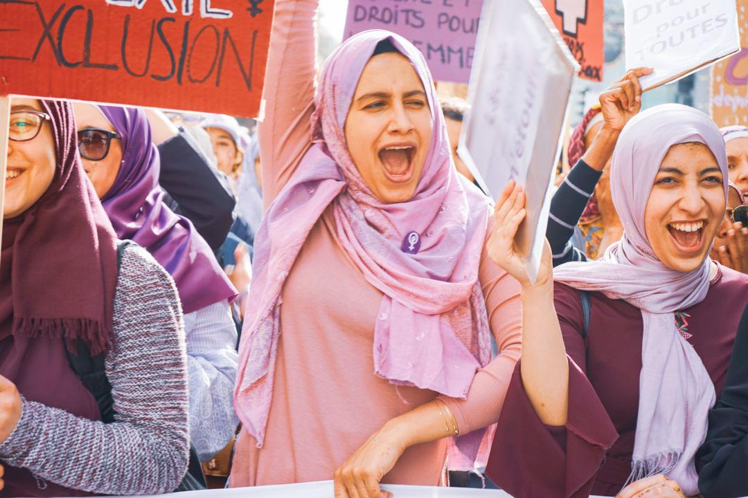 Drei Frauen mit lila und violettem Kopftuch an der 14.Juni 2019 Demonstration mit einem Transparent in der einen und jeweils Pancartas in der anderen hand, sie rufen kraftvoll