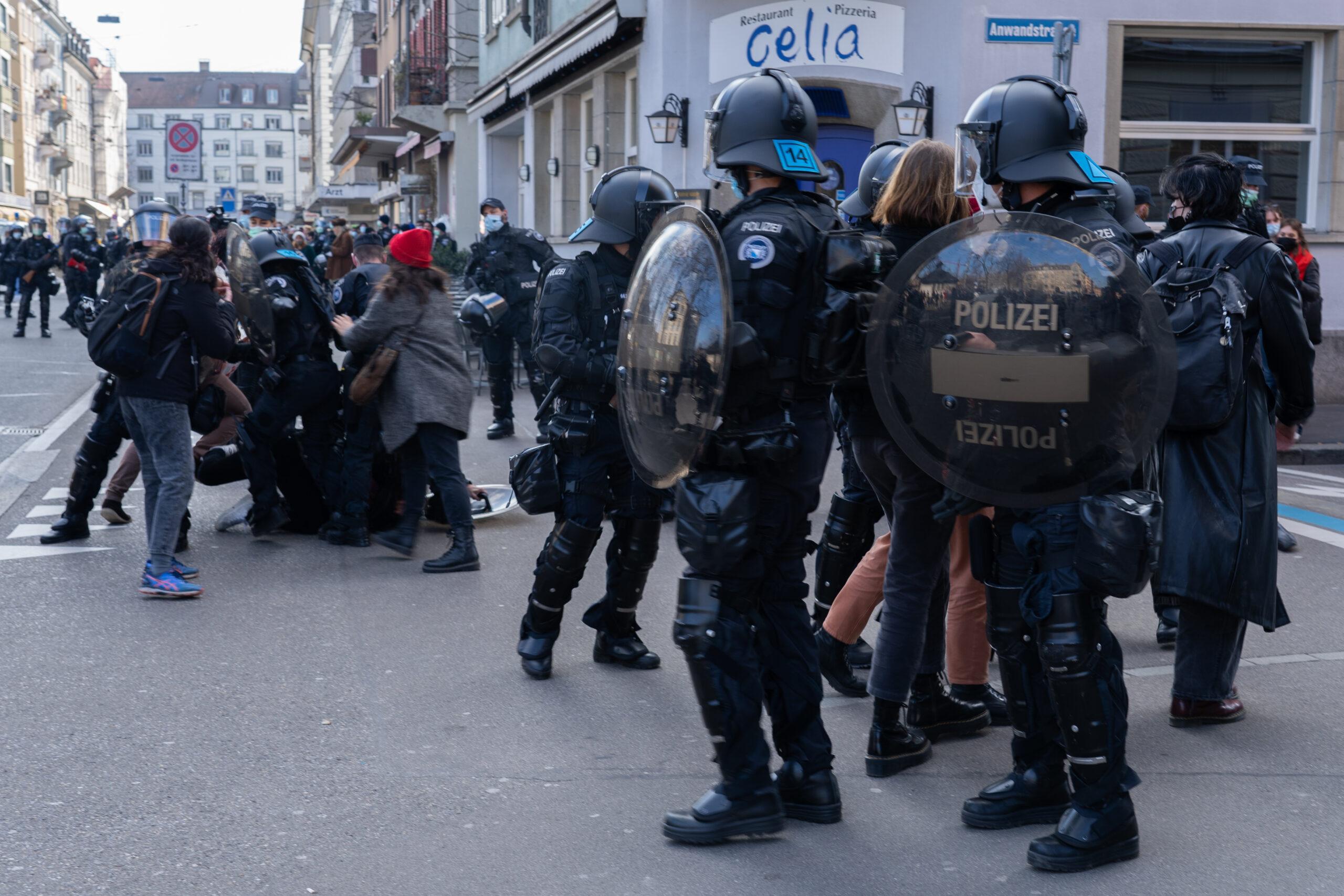 Ein Foto vom 6. März 2021 in Zürich, zwei Gruppen an Polizist_innen eine Gruppe führen Demonstrierende ab die andere Polizeigruppe drückt ein:e Aktivist:in zu Boden, andere Aktivist:innen wollen gegen die Polizei Helfen