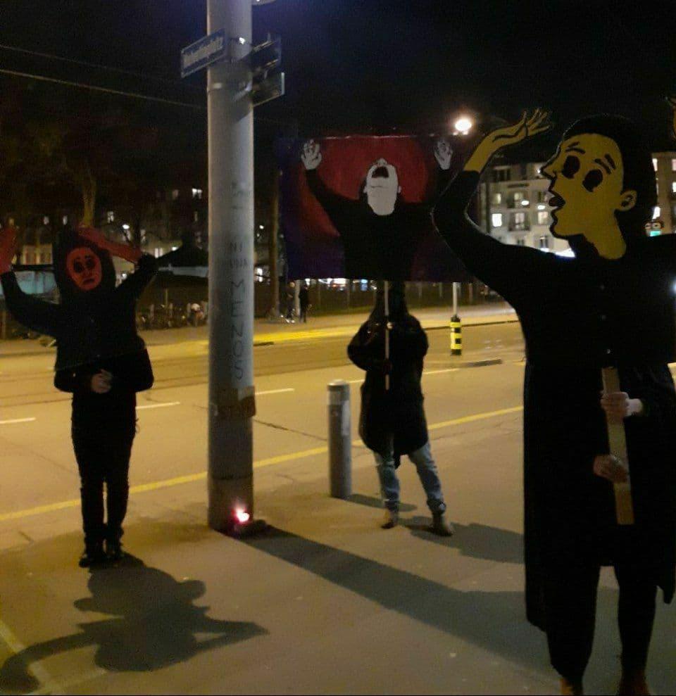 """Drei Personen mit """"Klageweiber""""-Masken nachts in Zürich."""