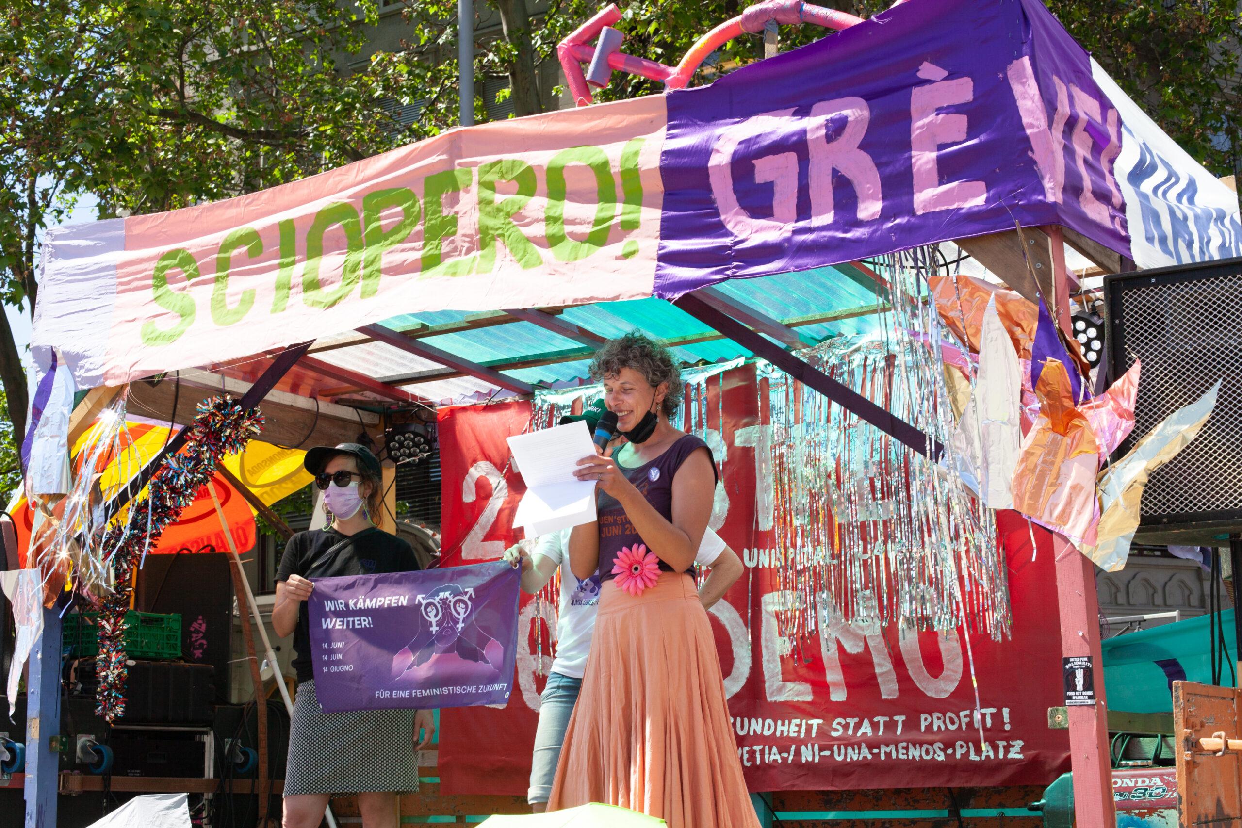 Der mit Bannern dekorierte Demo-Wagen. Zwei Personen auf der Bühne, das Banner des streikkollektiv hochhalten. Eine Person spricht ins Mikrofon während sie ein Blatt liest.