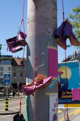 Schuhe, aufgehängt in Memoria an ermordete Frauen. Die Schuhe sind violett oder pink angemalt.