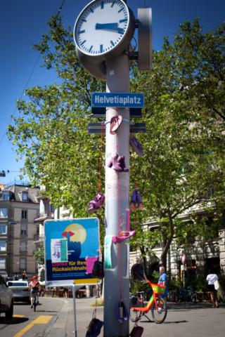 Die Uhr und Beschriftung des Helvetiaplatz mit allen 14 Schuhen, die in Memoria an ermordete FLINT*-Personen dieses Jahr in der Schweiz erinnert. Die Schuhe sind violett oder pink angemalt.
