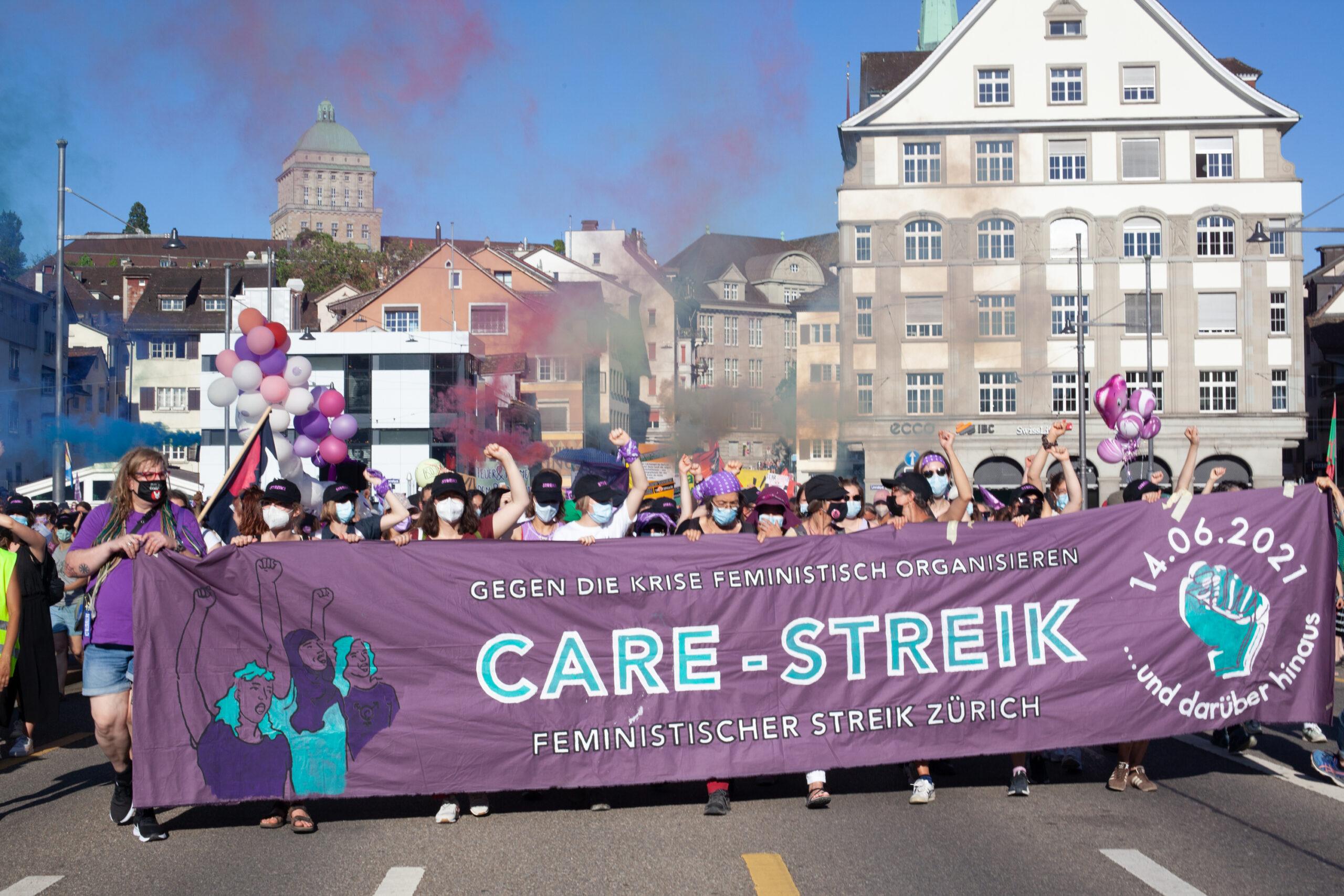 BIld der Demonstration auf der Rudolf-Brun-Brücke. Personen tragen das Frontbanner, auf dem steht: Gegen die Krise feministisch organisieren. CARE STREIK. Feministischer Streik Zürich. 14.06. 2021 ... und darüber hinaus.